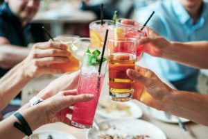 Group of friends clinking their drinks together.