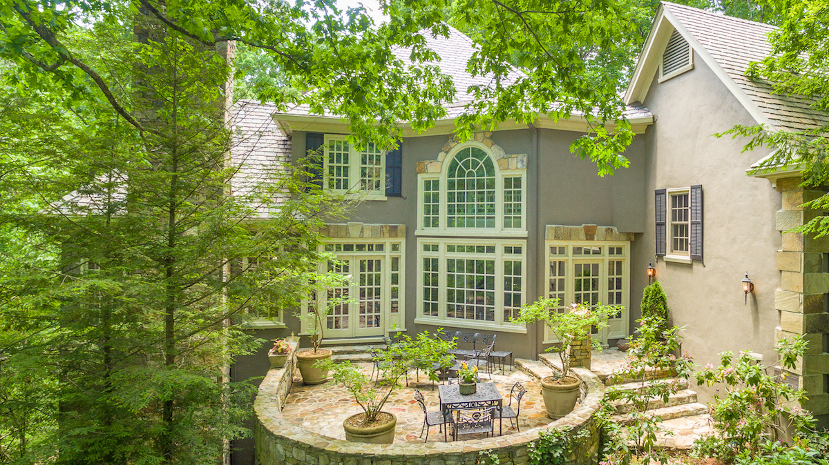 exterior of 2 story home with large windows and patio